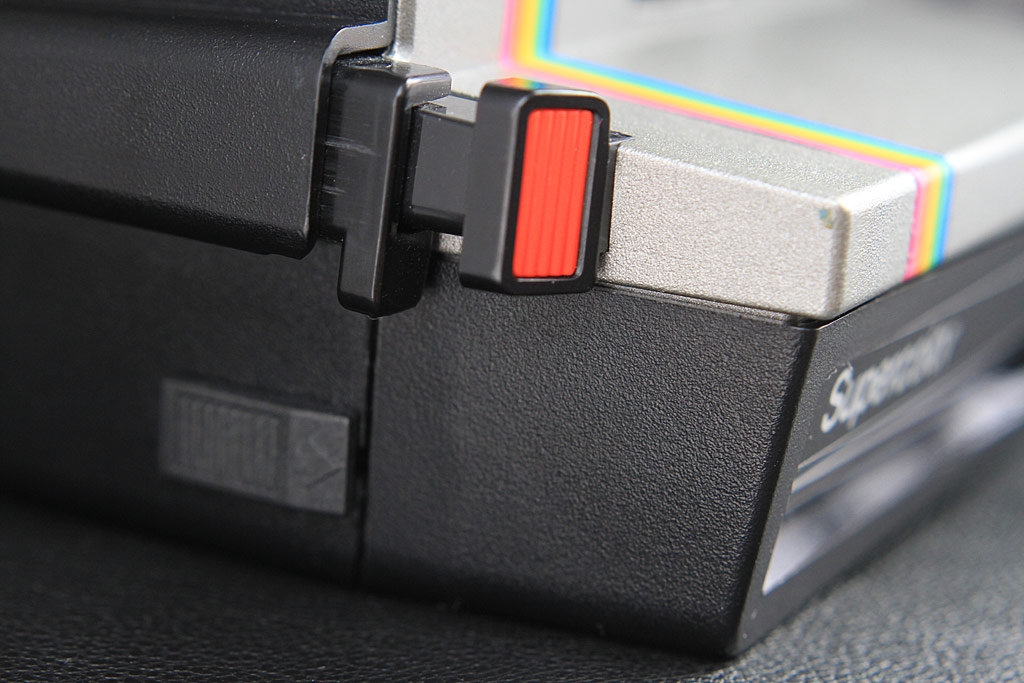 The shutter release for the Polaroid 635 Supercolor. By pressing the red button, the flash is activated if needed. By pressing a notch behind and below, the picture will be taken without flash.
