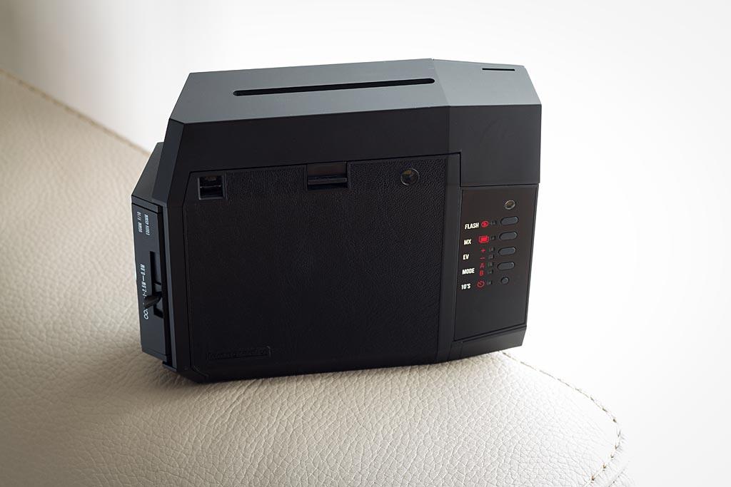 L'appareil, vu de dos. Les fonctions principales sont accessibles à travers une série de touches alignées sur la droite. Les photos sont expulsées par la fente centrale visible sur le dessus.