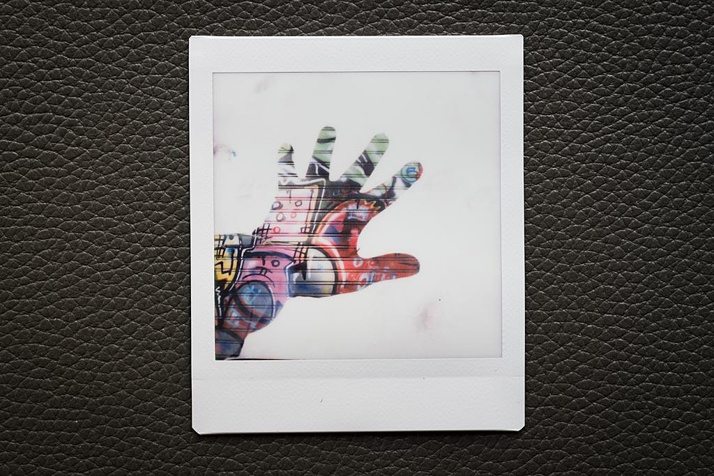 Le secret de fabrication de cette double exposition : un mur couvert de graffitis sur la première pose, et une main dans un gant noir, au-dessus d'un sol couvert de neige pour la seconde.