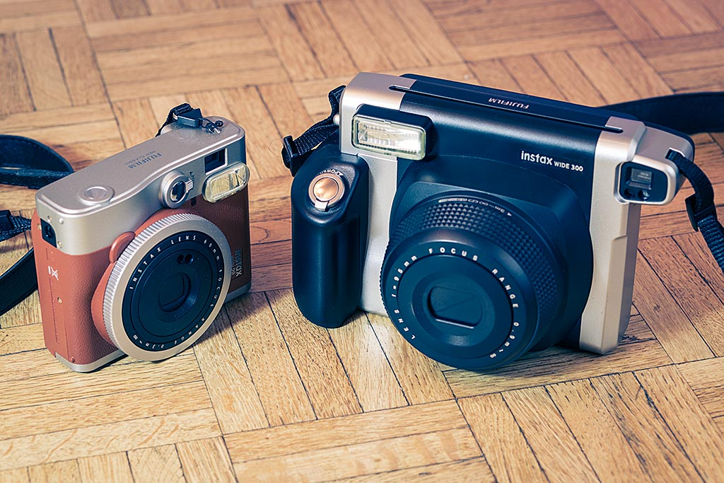 The Instax Mini 90 Neo Classic and the Instax Wide 300 side by side. The Wide is clearly an older brother in the Instax family.